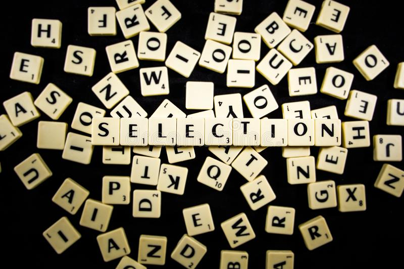Selection word spelled with letter tiles in black background royalty free stock image