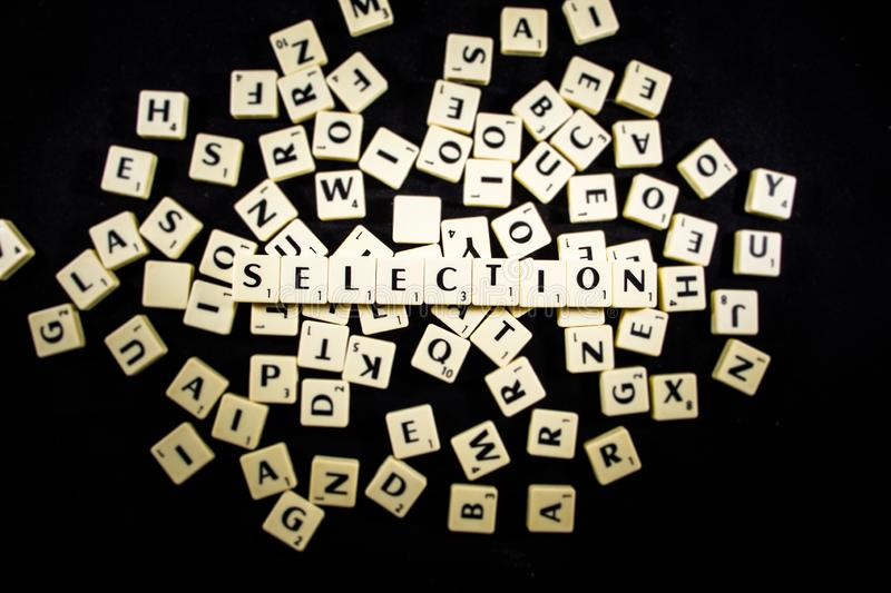 Selection word spelled with letter tiles in black background stock photos