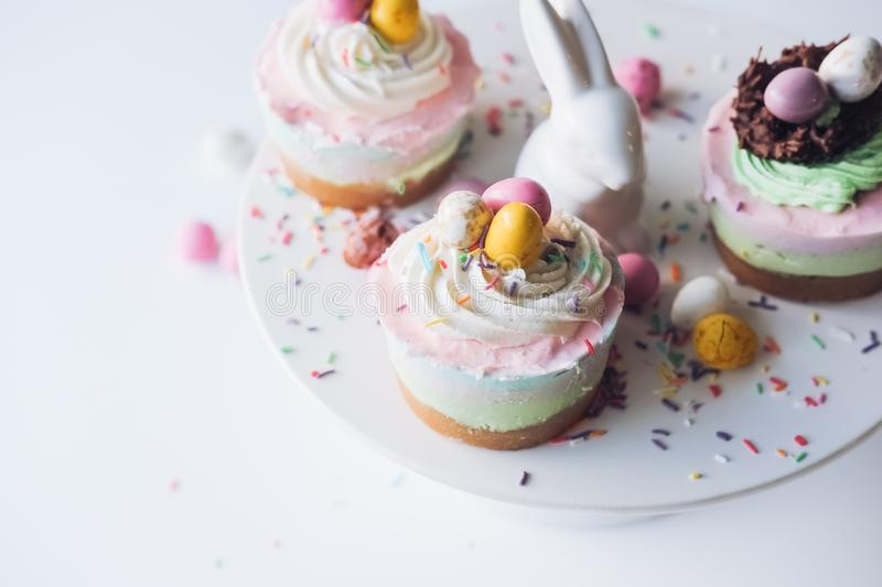 Selective closeup shot of Easter bunny and cupcakes on a white ceramic cake stand royalty free stock photography