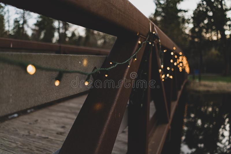 Selective closeup shot of lighted string lights on a brown wooden bridge. A selective closeup shot of lighted string lights on a brown wooden bridge royalty free stock images
