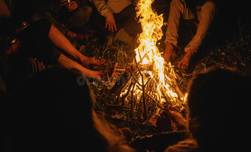 Selective closeup shot of people warming up while sitting around a lighted bonfire royalty free stock photography