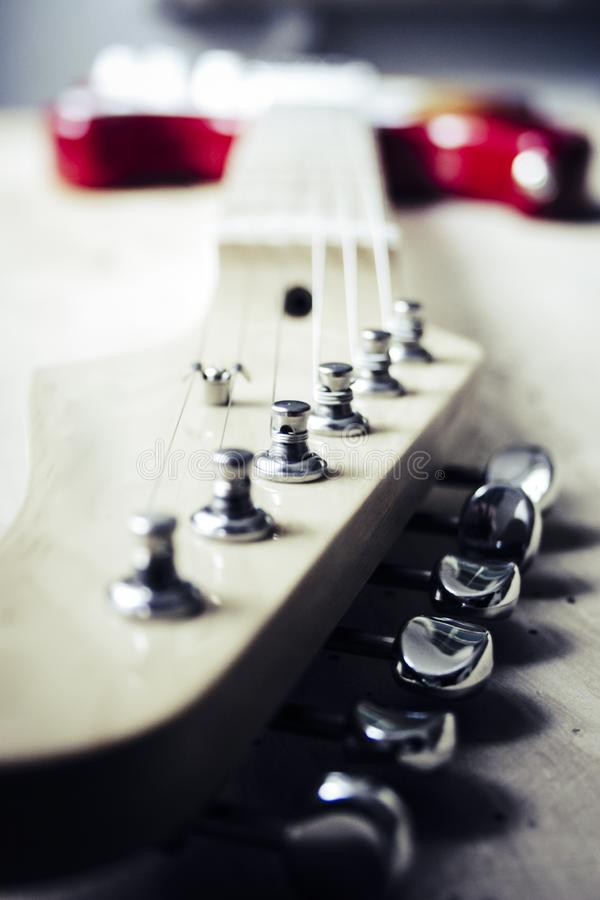 Selective closeup shot of a tailpiece of a white and red electric guitar royalty free stock photos