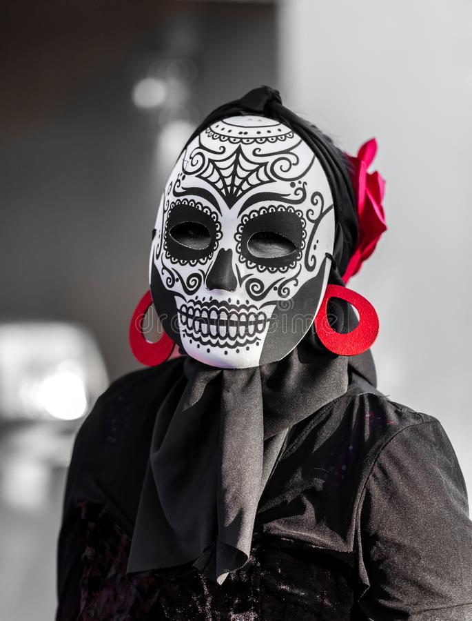 Selective color, black and red, portrait of woman wearing a sugar skull mask for dia de los muertos / day of the dead celebrated stock images