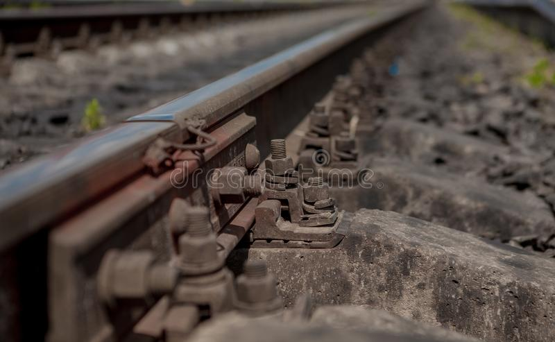 Selective field of focus. Detail of rusty screws and nut on old railroad track. Concrete tie with rusty nuts and bolts. Damaged su stock image