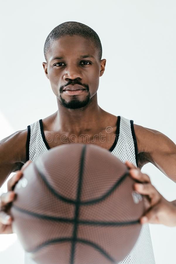 Selective focus of african american basketball player holding ball. Isolated on white stock photography