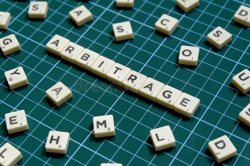 Selective focus of Arbitrage word made of square letter block on green square mat background.  royalty free stock photos