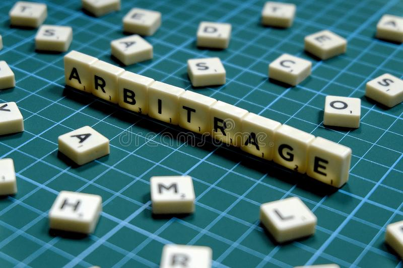 Selective focus of Arbitrage word made of square letter block on green square mat background.  royalty free stock images