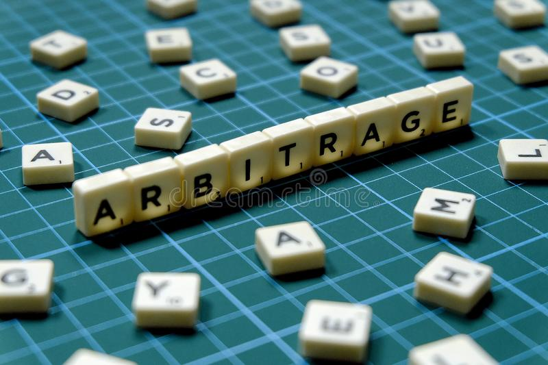 Selective focus of Arbitrage word made of square letter block on green square mat background.  stock photography