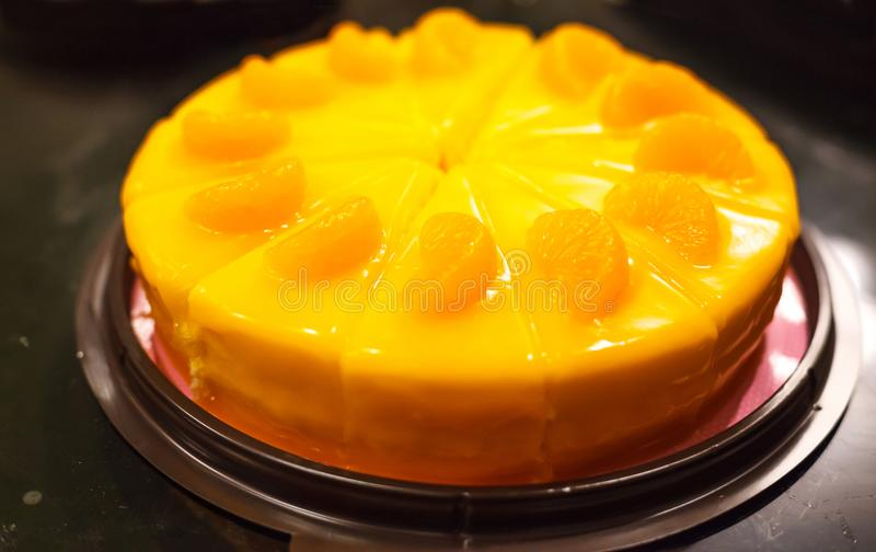 Selective focus on bakery dessert, orange color cake with orange mousse and orange fruit toppings on black glass table background stock images