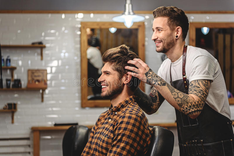 Selective focus on barber with client. Close up of professional hairdresser and his customer in hair salon stock image