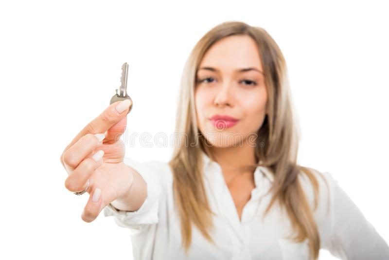 Selective focus beautiful business real estate woman showing apartment key. Isolated on white background with copy space advertising area royalty free stock image