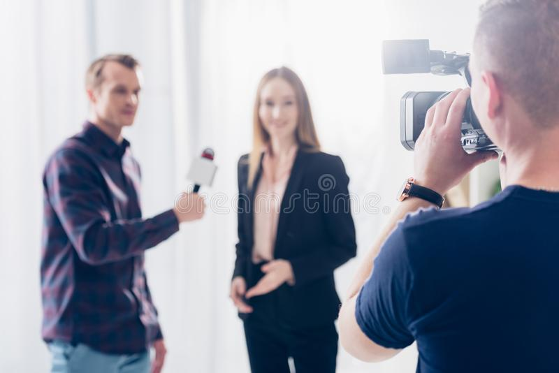 Selective focus of beautiful businesswoman in suit giving interview to journalist. In office stock photography