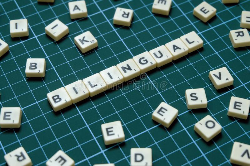 Selective focus of Bilingual word on square green mat background.  stock images