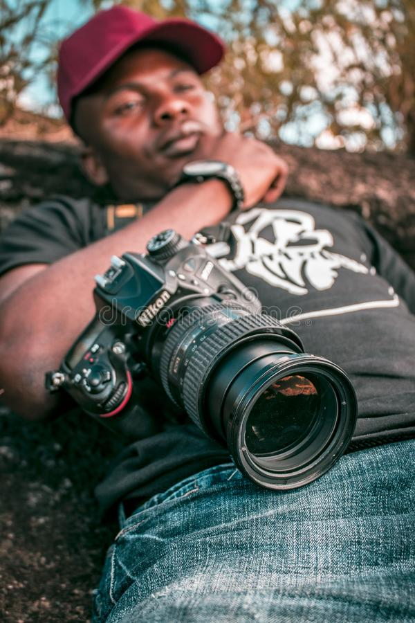 Selective Focus Black Nikon Dslr Camera With Zoom Lens on Lap Photo royalty free stock images