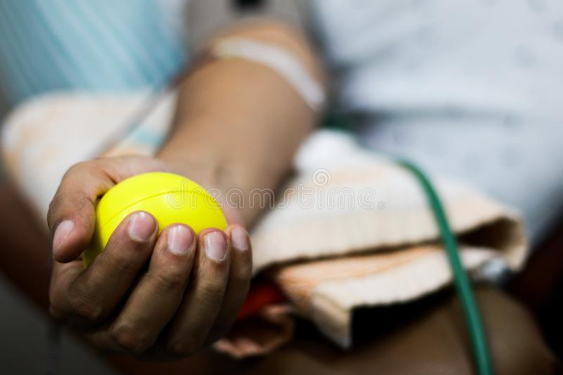 Selective focus of blood collection during blood donation and ball in palm for squeezing stock photography