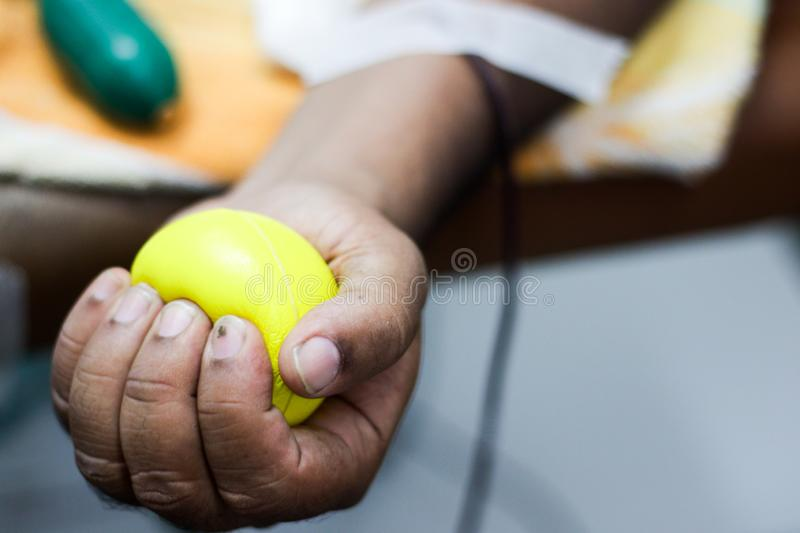 Selective focus of blood collection during blood donation and ball in palm for squeezing royalty free stock image