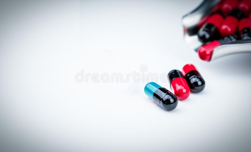 Blue-green capsule pill and drug tray with red-black capsule. Global healthcare. Antibiotics drug resistance. Antimicrobial. Selective focus blue-green capsule royalty free stock photos
