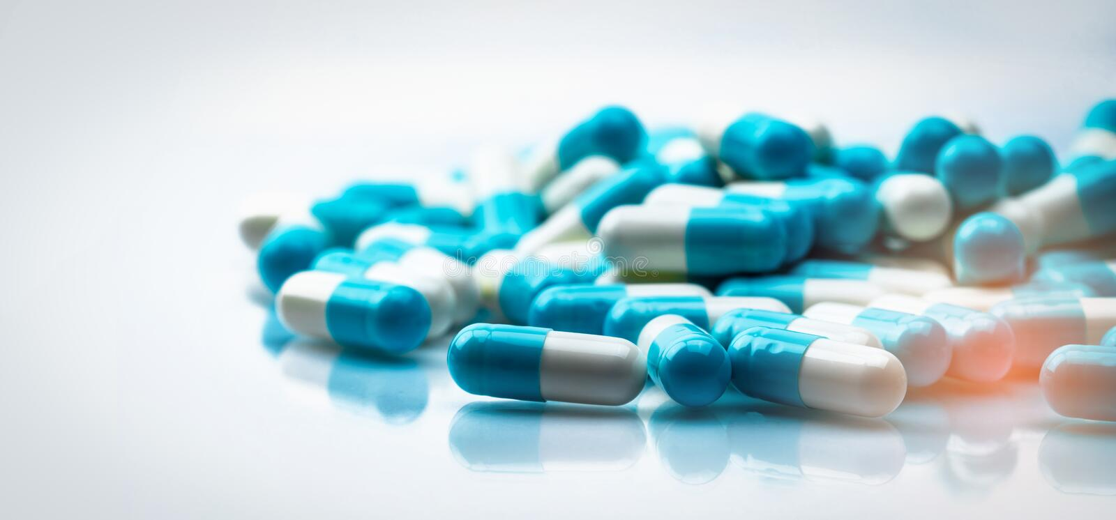 Selective focus on blue and white capsules pill spread on white background with shadow. Global healthcare concept. Antibiotics. Drug resistance. Antimicrobial royalty free stock photos