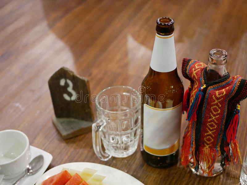 Bottles of opened beer and water in a Khantok dinner, Northern Thai style meal which people sit and eat on a floor stock photography