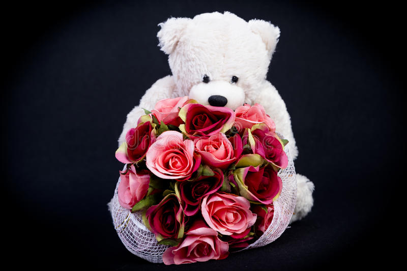 Selective focus at bouquet of red roses on white bear doll stock photography