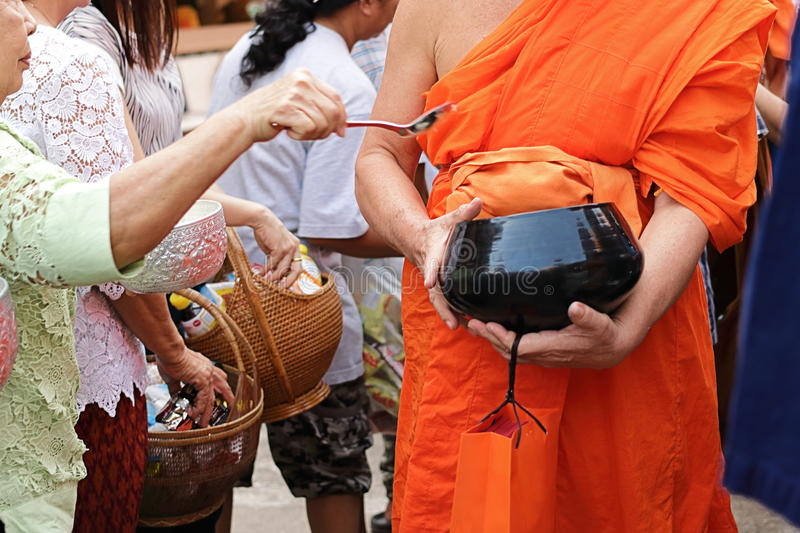 Selective focus on bowl. Thai people put food to a Buddhist monk`s alms bowl in Songkran festival Day.  stock photography