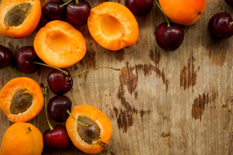 Cherries and apricot halves with seeds. Selective focus,bright, Mature apricots, seeds and berries ripe cherry on a wooden Board textured with drips stock photo