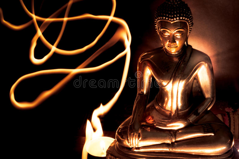 Selective focus of buddha statue with blurred burning candle light in soft night light. Concept of peace, meditation, hope and re. Selective focus of buddha royalty free stock photo