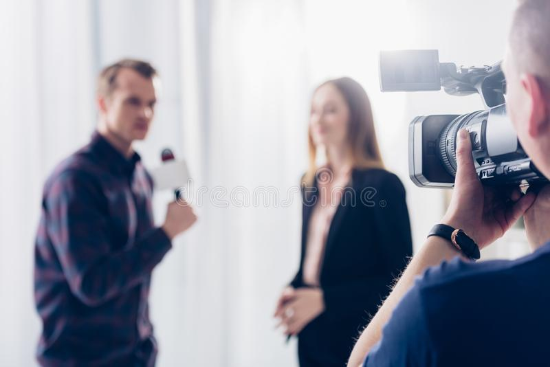 Selective focus of businesswoman in suit giving interview to journalist in office, cameraman. On foreground stock image