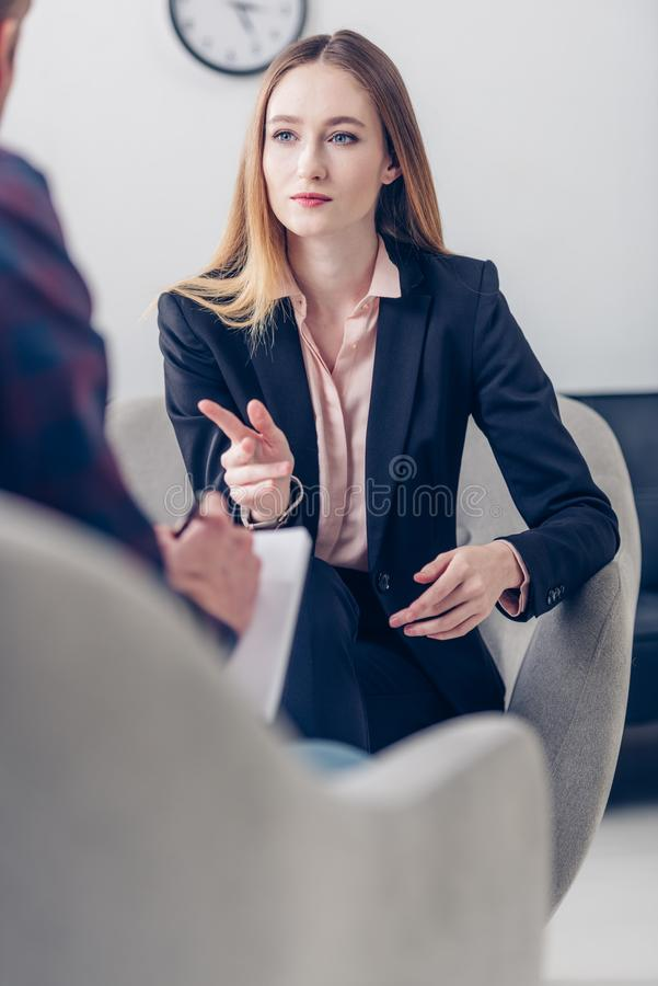 Selective focus of businesswoman in suit giving interview to journalist and pointing on him. In office royalty free stock photography