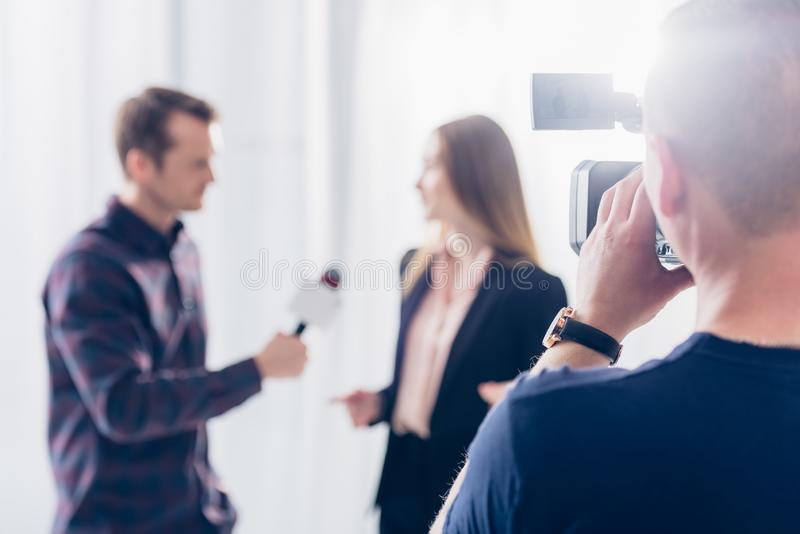 Selective focus of businesswoman in suit giving interview to journalist. At workspace stock photos