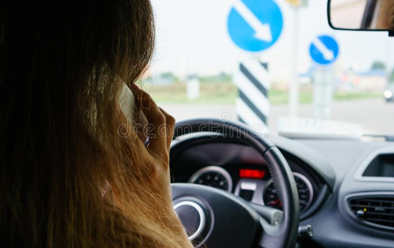 Selective focus on businesswoman talking on the smart phone while driving a car, rear view stock photography