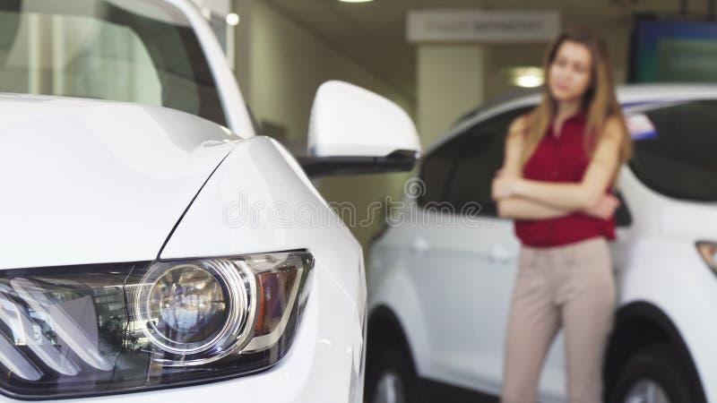 Female customer examining new car at the dealershop royalty free stock image