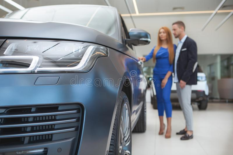 Young classy couple buying luxurious car at the dealership. Selective focus on car lights, classy elegant couple on background looking inside a new automobile on stock image