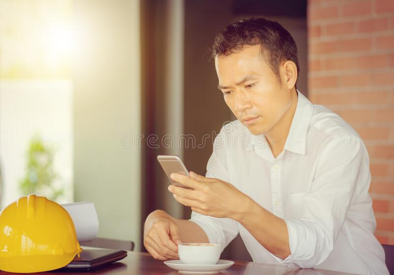 Casual young business engineer man hand using mobile smart phone with coffee blurred background stock photos