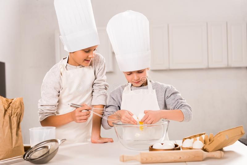 Selective focus of in chef hats and aprons whisking eggs in bowl at table. In kitchen stock photography