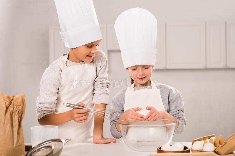 Selective focus of children in aprons and chef hats during food preparation at table. In kitchen stock photos