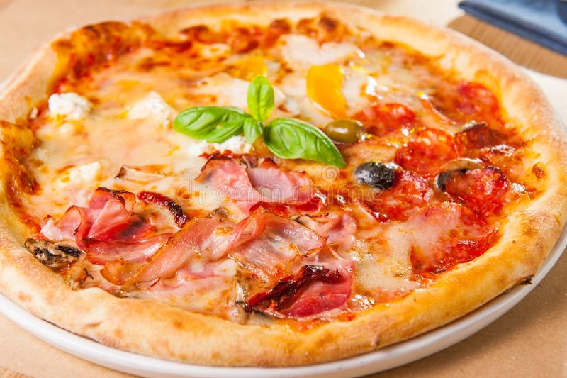 Selective focus close up Delicious Meat Pizza with bacon and sausages on white plate on the wooden table with cutlery and stock images