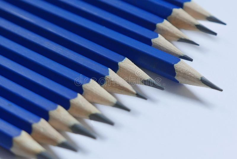 Selective focus and close up of one blue pencil standing out from the row on white background. royalty free stock photography