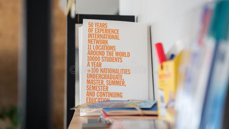 Selective focus closeup shot of a white board with orange text on a bookshelf. A selective focus closeup shot of a white board with orange text on a bookshelf royalty free stock image