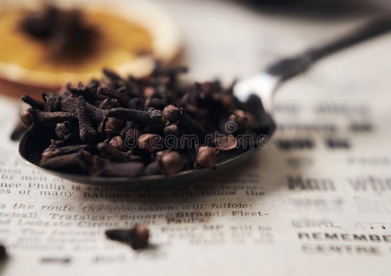 Selective focus on cloves in vintage spoon on vintage newspaper. Soft focus background with orange and star anise on the top. stock photography
