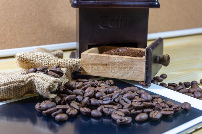 Selective focus coffee beans on tablets, grinded beans in vintage wooden coffee grinder and sackcloth royalty free stock images