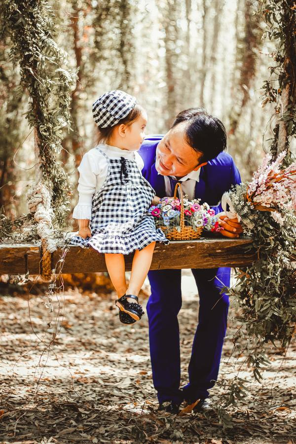 Selective Focus and Color Photography of Man Looking at Her Girl Sitting on Garden Swing White Holding Bouquet of Flower in Brown royalty free stock photo