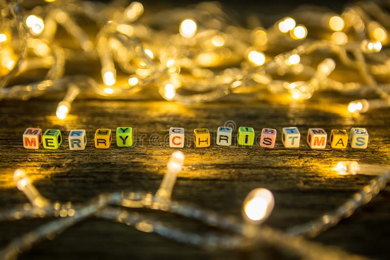 Selective focus of Colorful Alphabet beads. `Merry Christmas` and LED lights on wooden floor background royalty free stock image