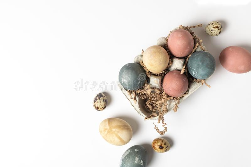 Selective focus of coloured decorated easter eggs in cardboard container, minimal on white royalty free stock image