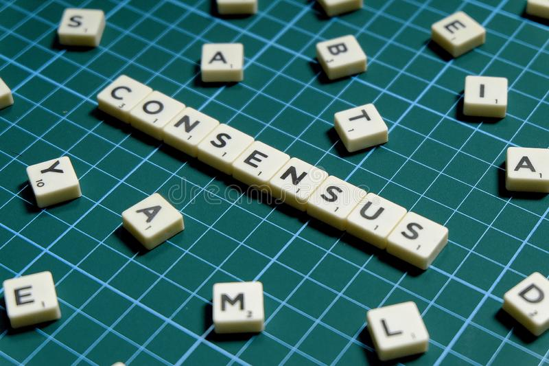 Selective focus of Consensus word made of square letter block on green square mat background.  stock photos