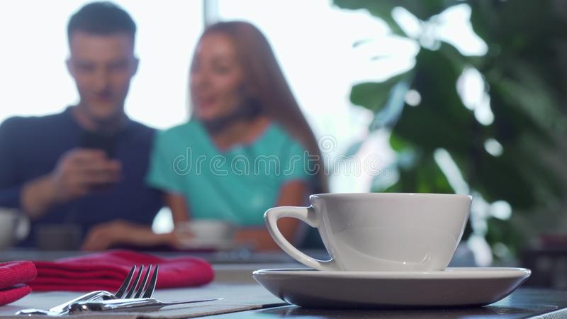 Selective focus on a cup on the table, couple cuddling on the background royalty free stock photography