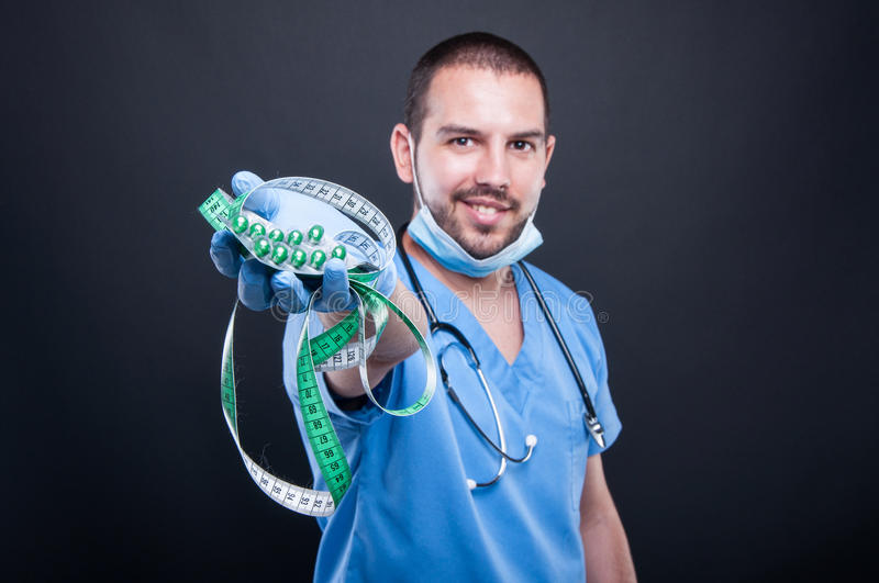 Selective focus of doctor holding pills and measuring tape royalty free stock images