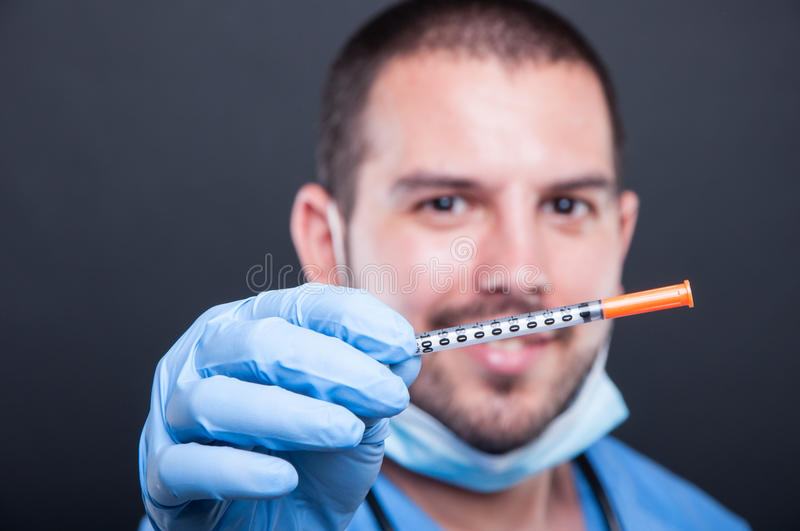 Selective focus of doctor wearing scrubs holding diabetes inject royalty free stock image