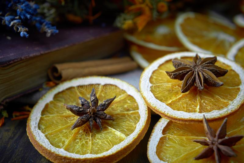Selective focus on dry oranges with star anise on the top. Soft focus background with old book, cinnamon, lavender stock images