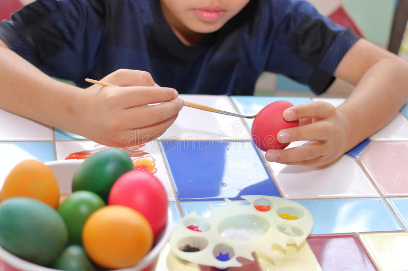 Selective focus. Egg is being painted with little boy for prepareing easter day. stock image